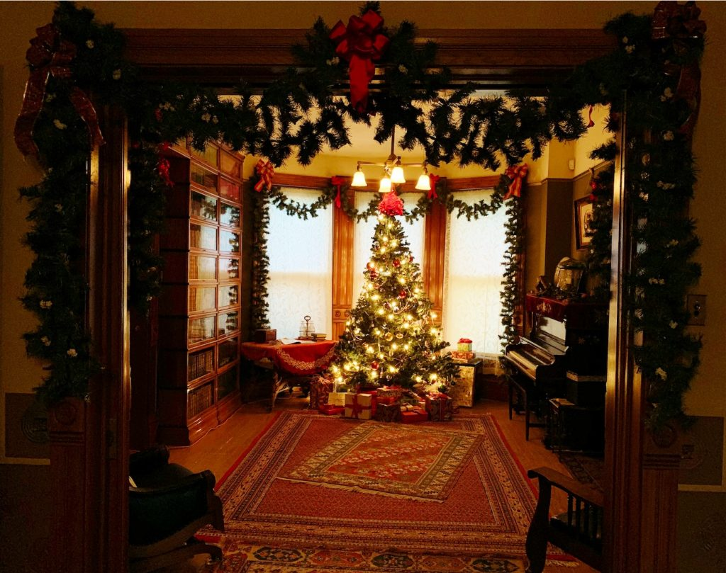 Christmas tree with white light in bay window with evergreen garland around entry.