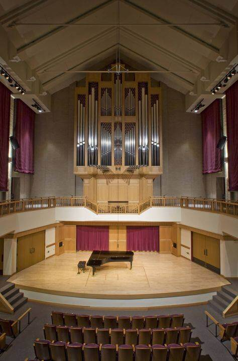Pipe organ surrounding stage with grand piano